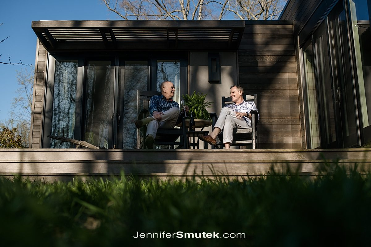 two men sitting on a porch drinking wine