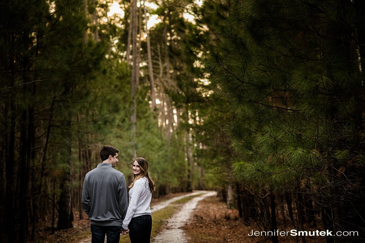 couple walking down wooded path