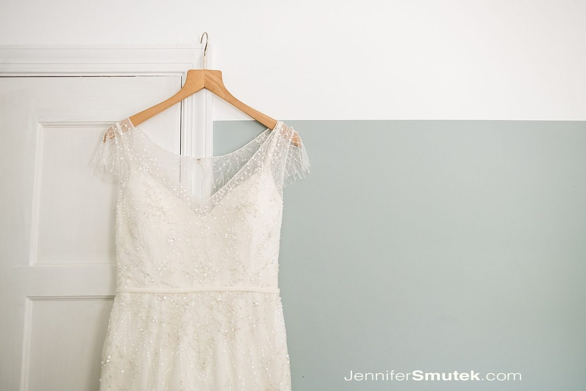 vintage wedding dress hanging on door