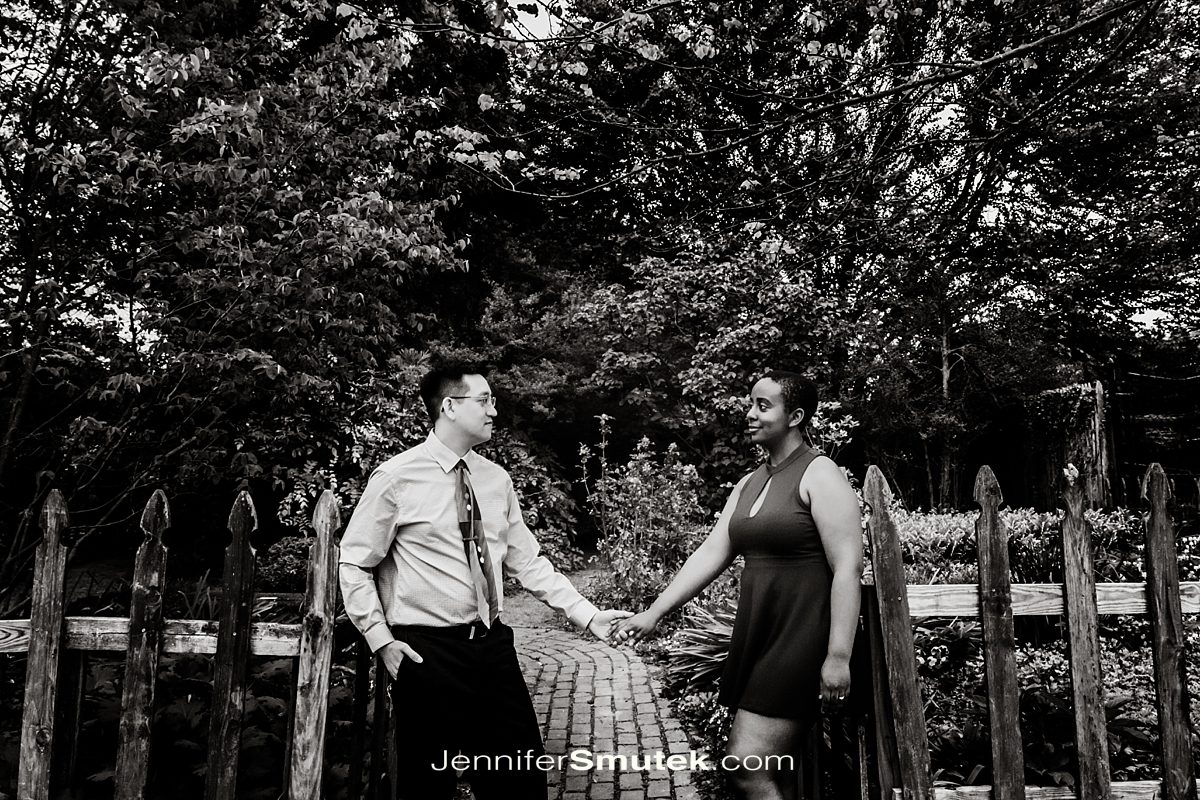 black and white photo of couple in fence opening
