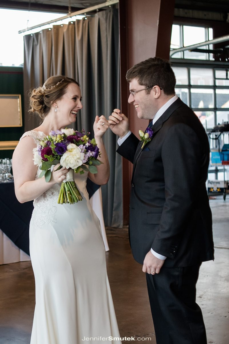 couple pinkie swearing after wedding