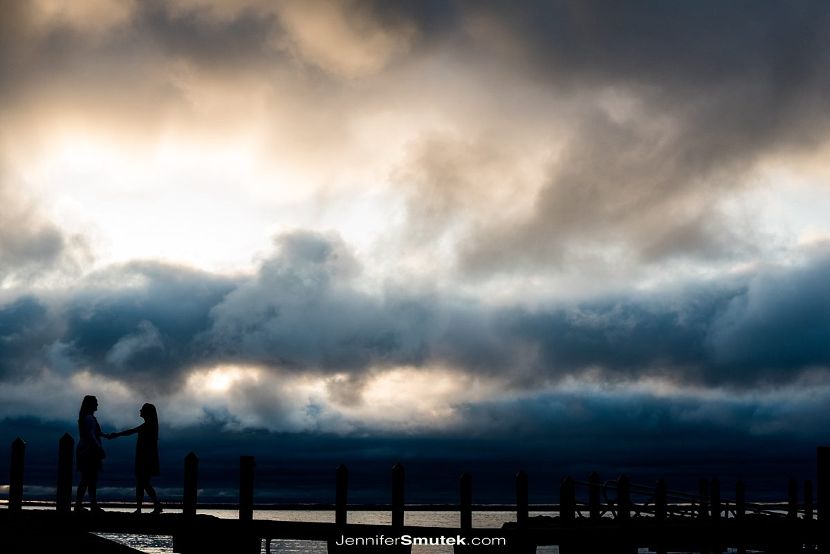 two brides walking along a pier at sunrise
