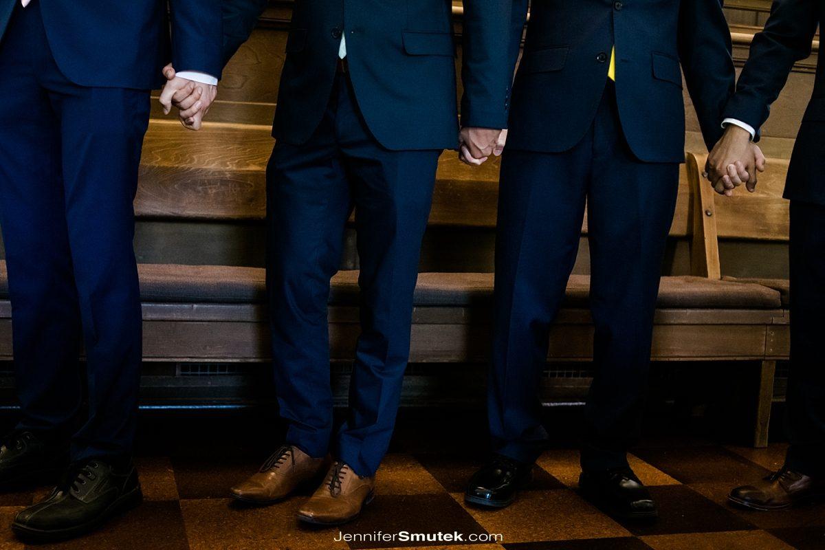 groomsmen holding hands