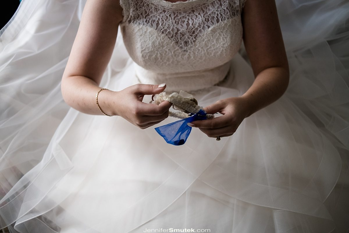 bride holding her garter and something blue