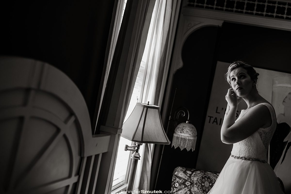 black and white photo of bride getting dressed at the Vandiver Inn