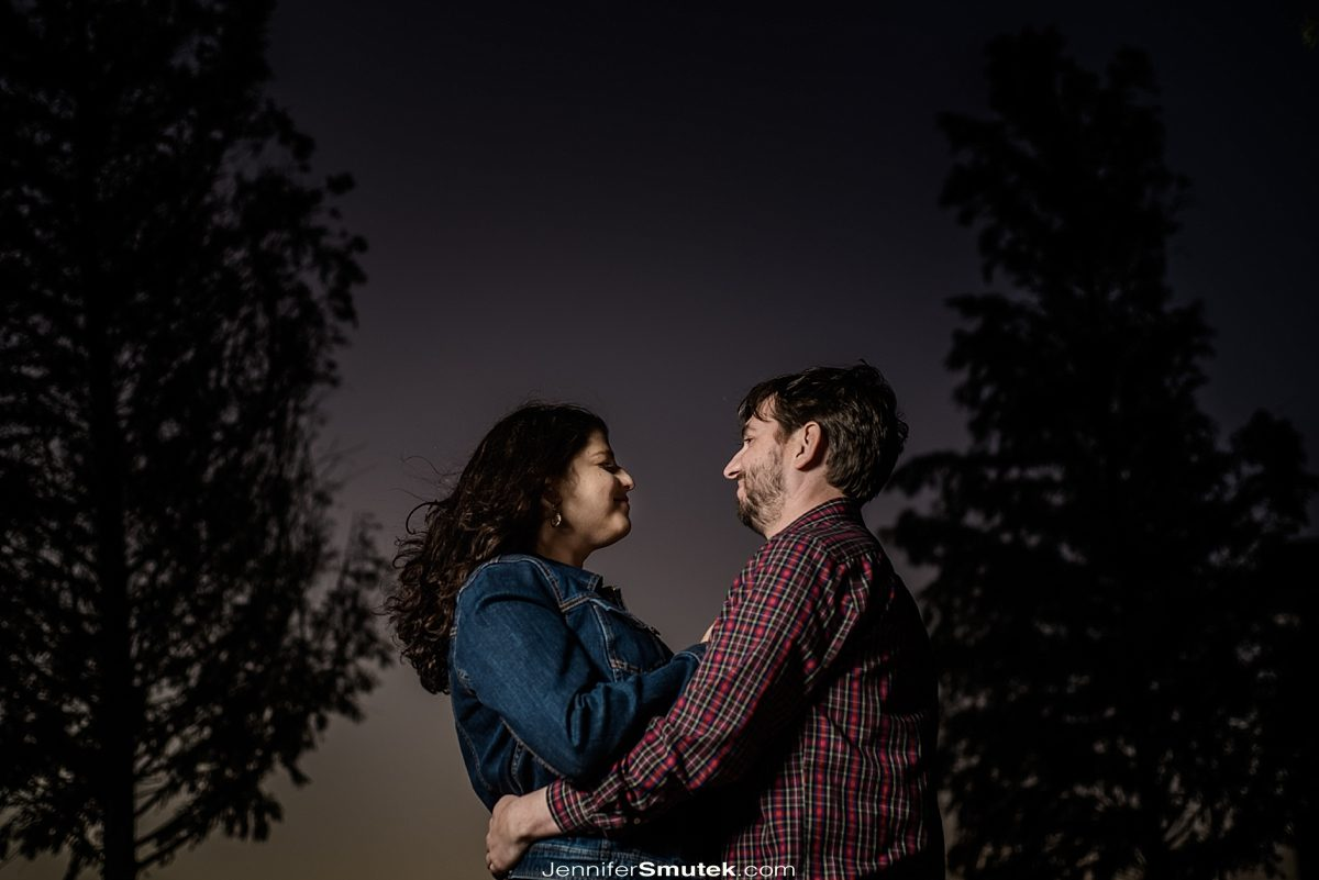 couple standing between two trees in their baltimore engagement photos