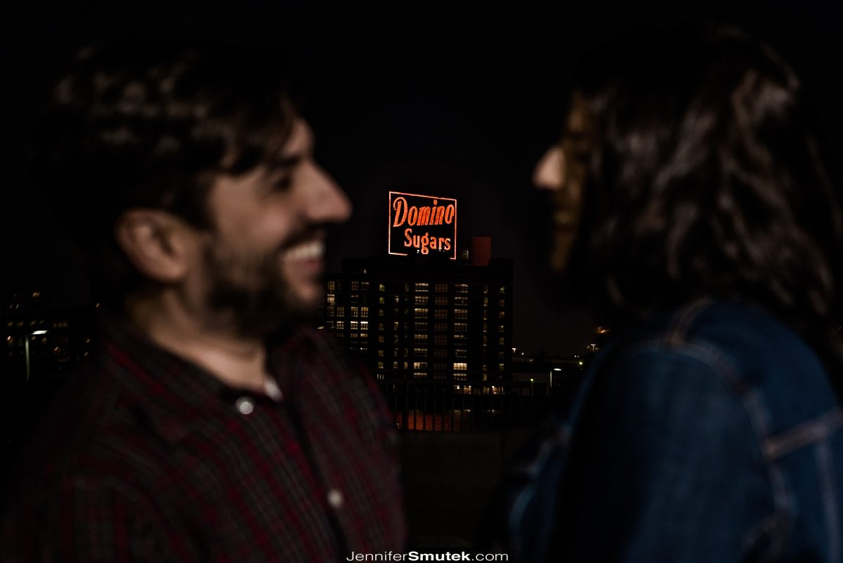 couple laughing with domino sugar sign
