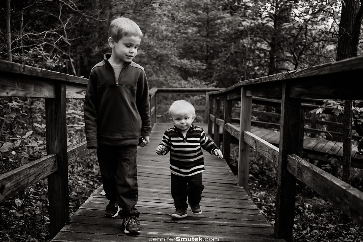 black and white photo of two brothers walking on a wooden walkway Downs Park Family Photography