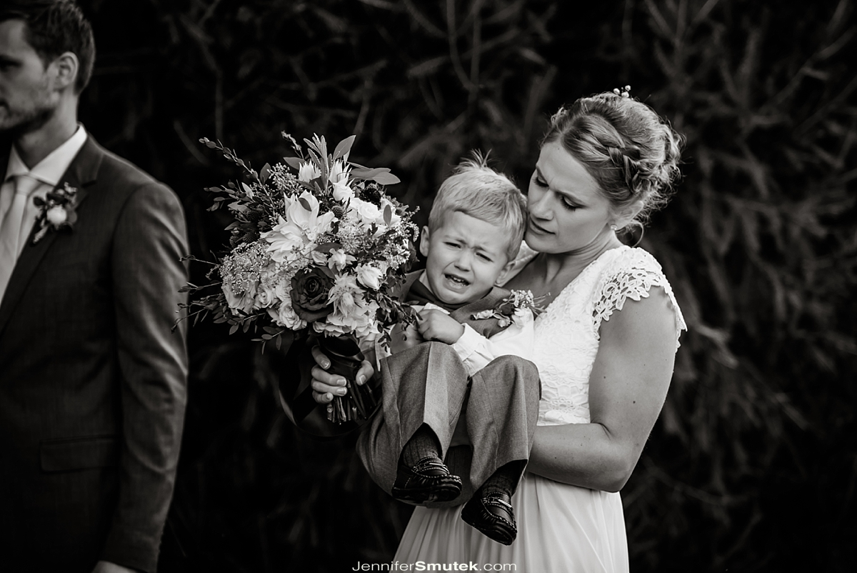 bride holding crying ring bearer