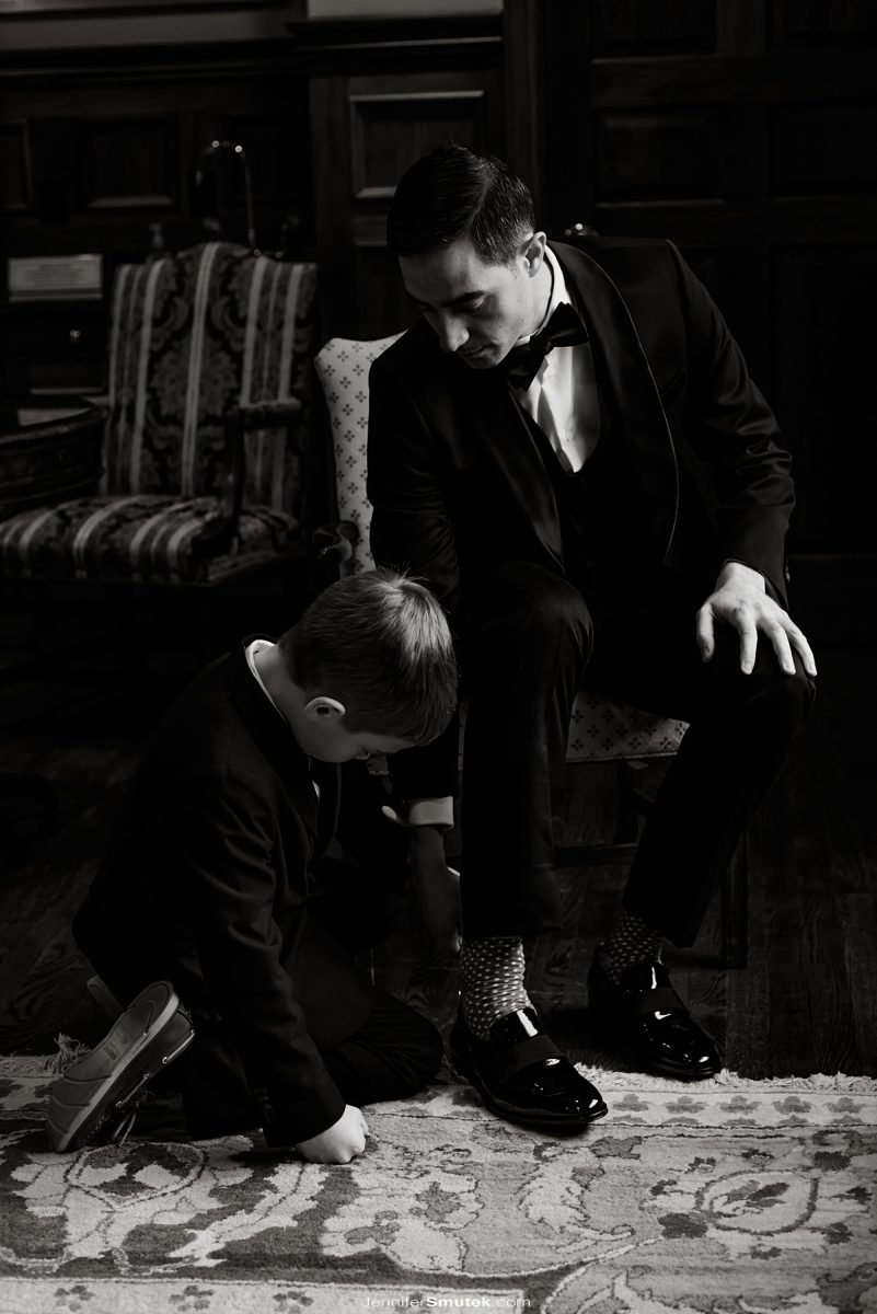 young boy helping a groom put on his shoes