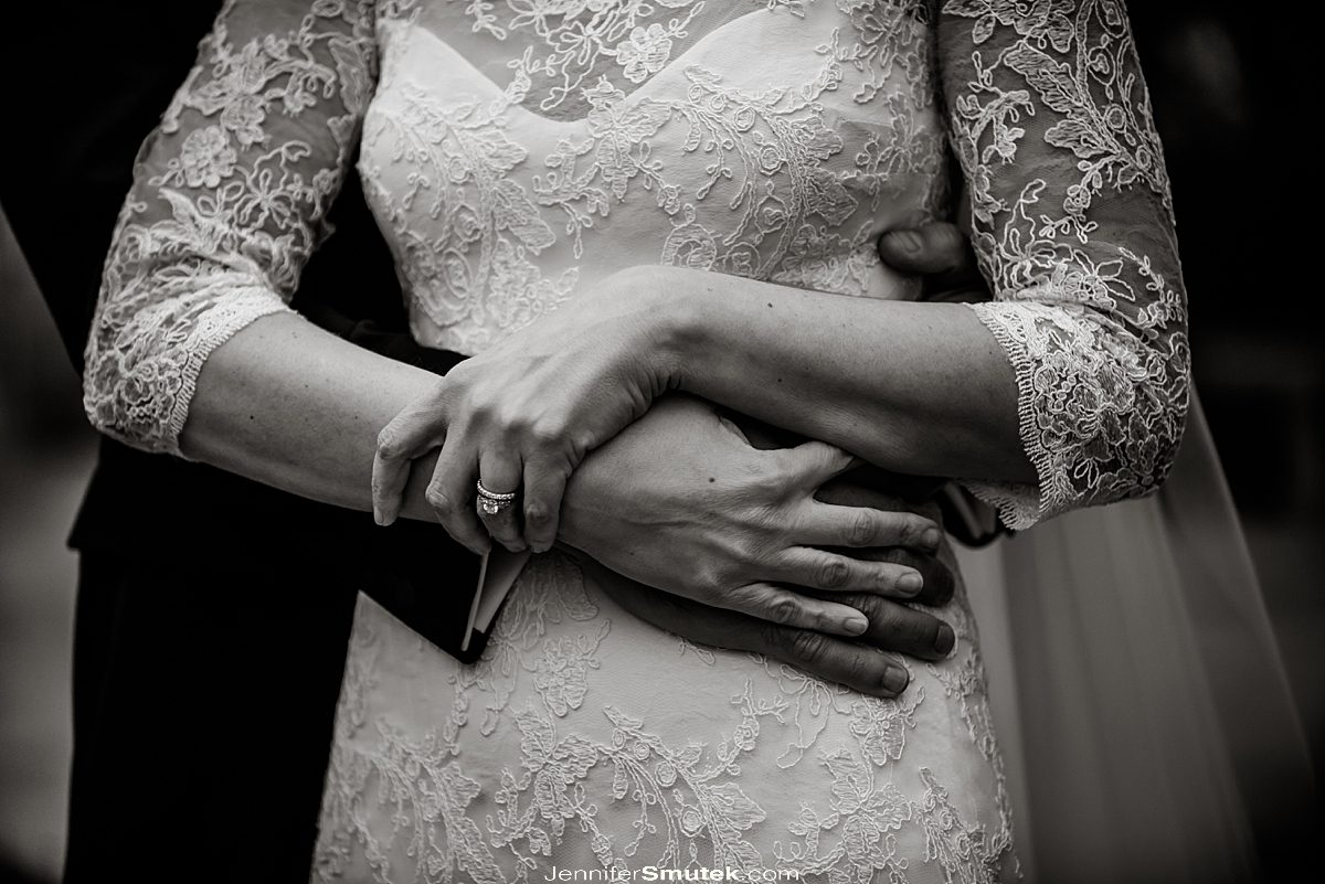 close up of lace wedding gown and couples hands