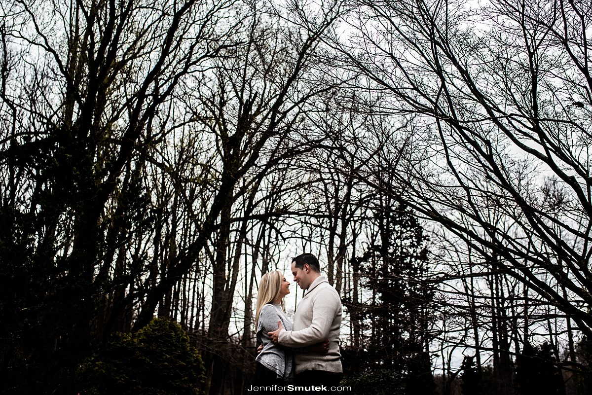 couple standing against winter trees Brookside Gardens spring engagement session