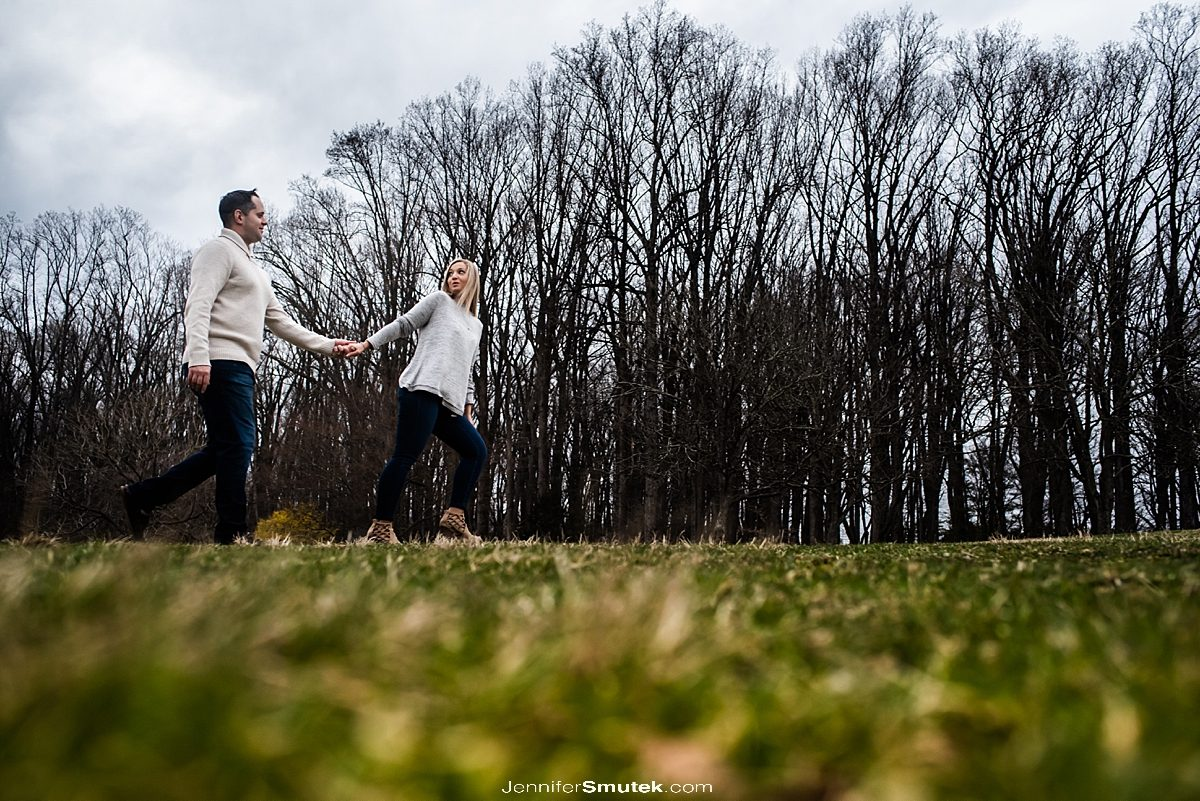 couple walking on a field in front of trees