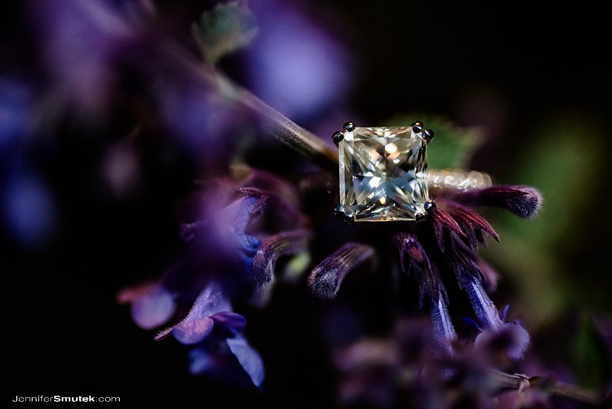 close up of princess cut engagement ring on purple flowers