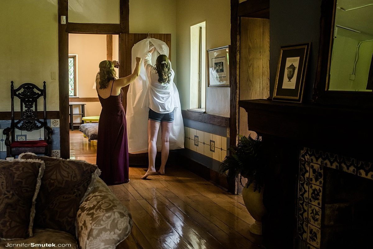 bride and bridesmaid taking dress out of the dress bag at the cloisters castle in maryland