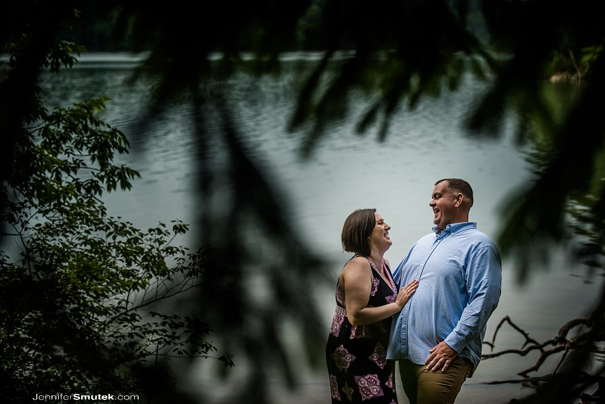 couple laughing between trees and near the water on their Loch Raven Reservoir Engagement Session