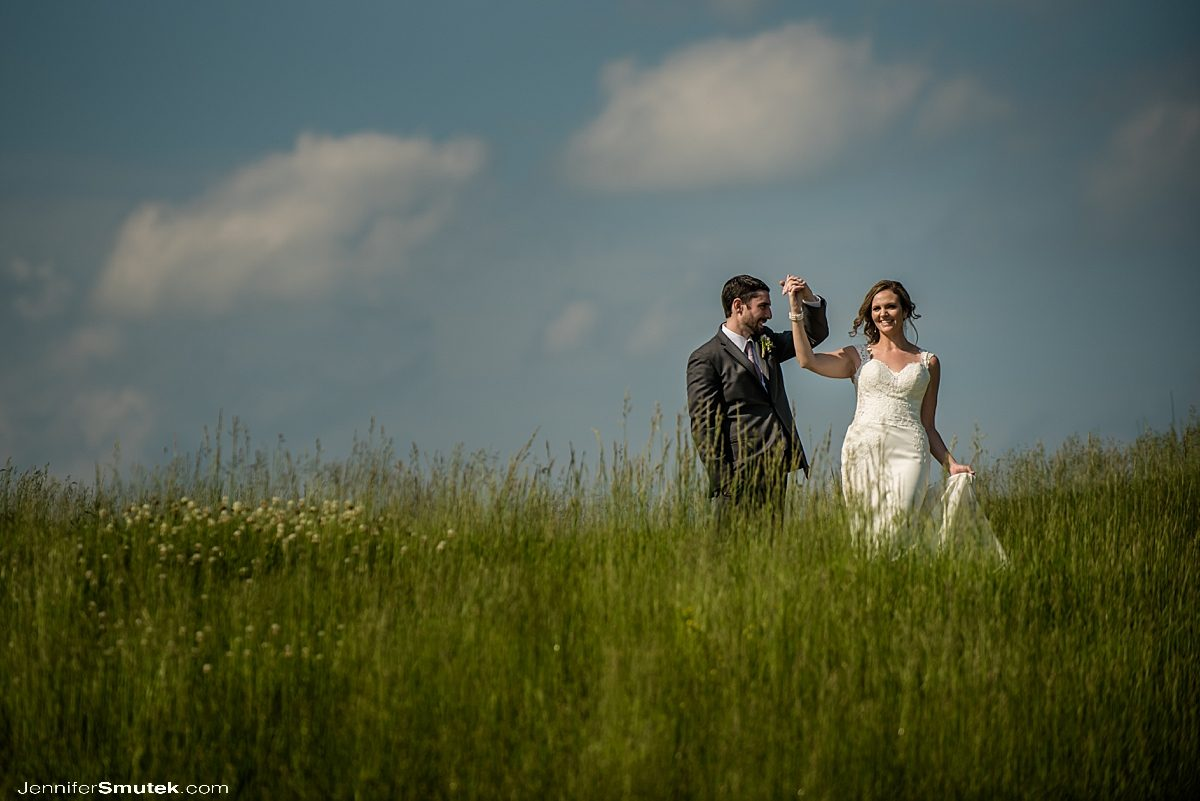bride and groom dancing in field