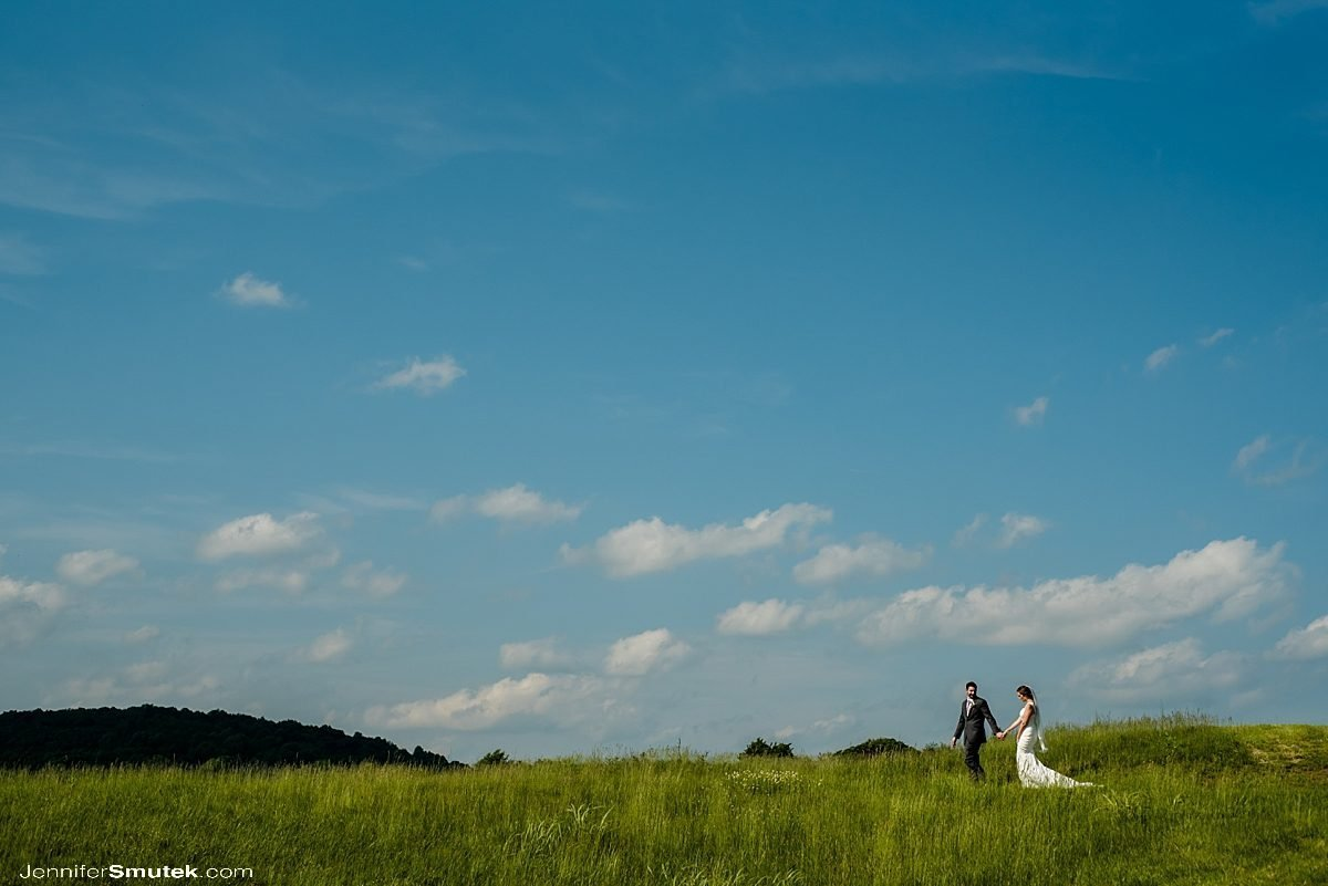bride and groom walking along the skyline Musket Ridge Golf Club Wedding