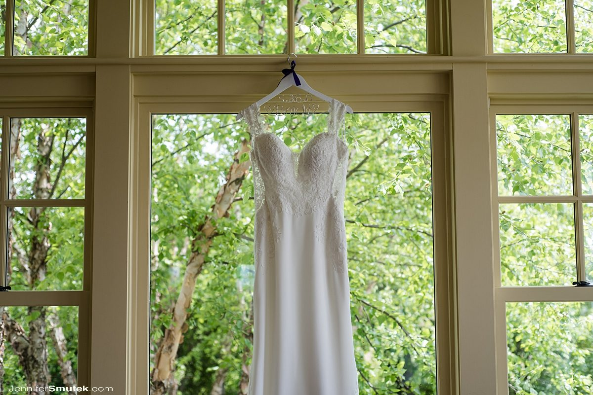 bridal gown hanging in window of Musket Ridge Golf Club Wedding