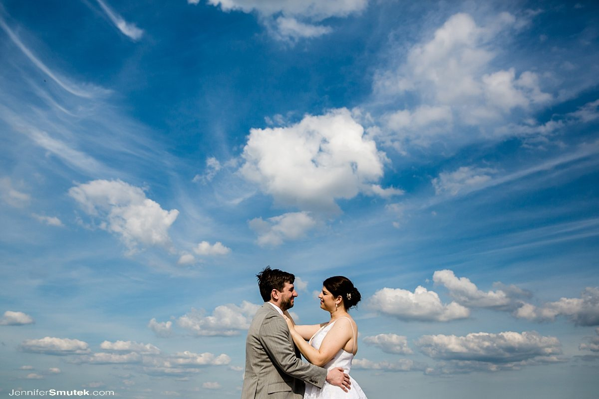 wide angle image of bride and groom in front of clouds