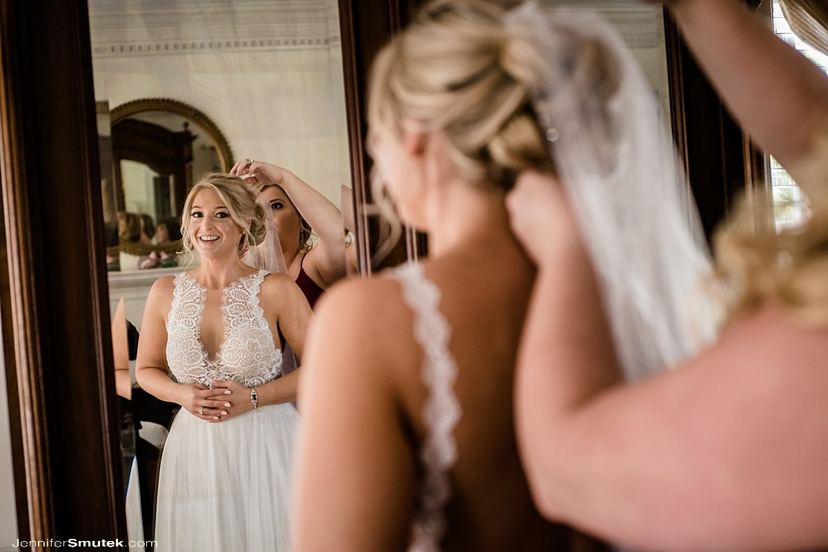 bride looking in mirror while putting on veil