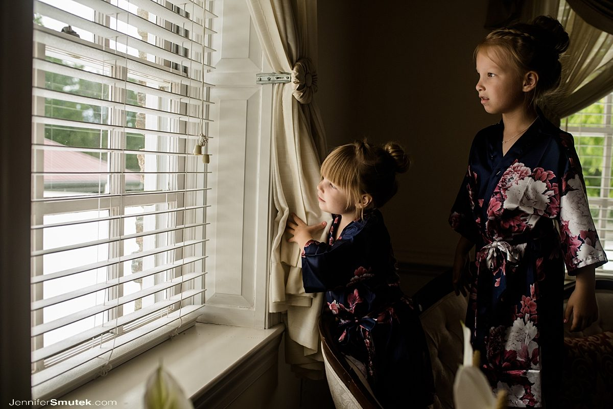 flower girls looking out of window at stone manor country club