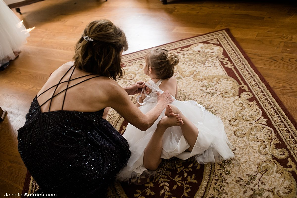 grandma helping flower girl get dressed
