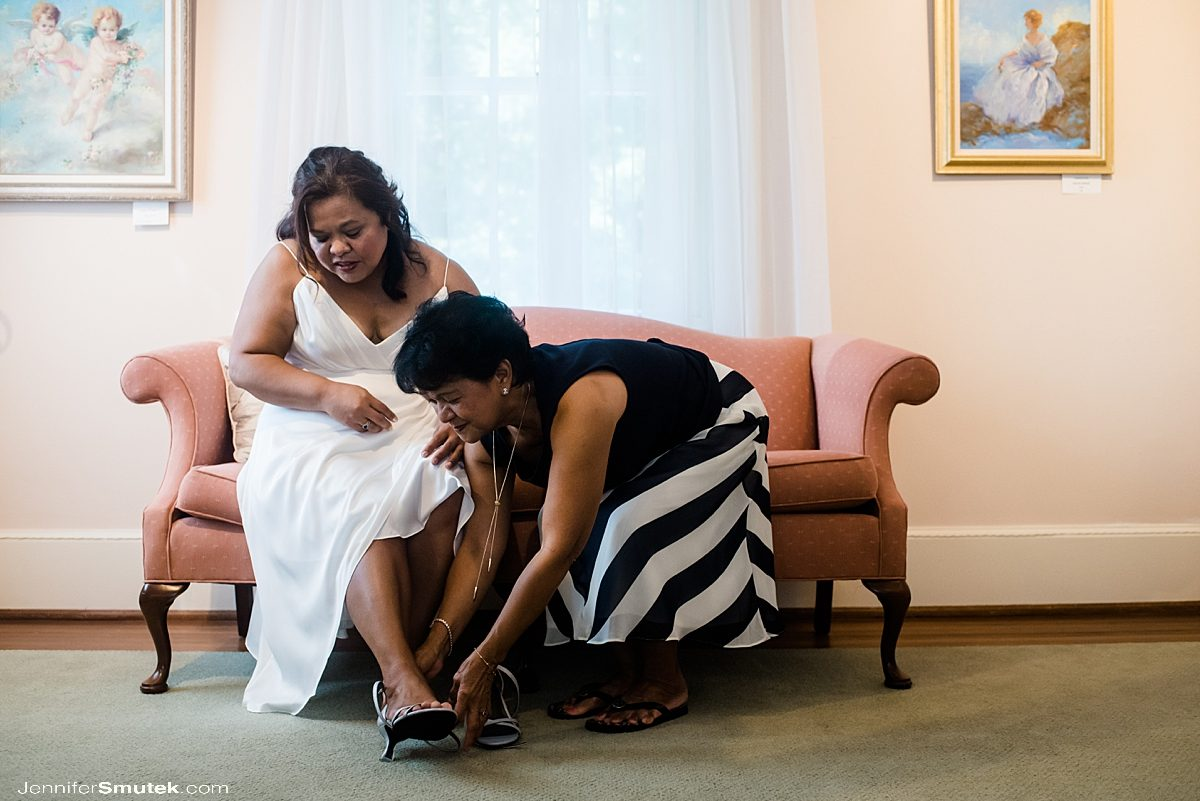 mother helping bride with shoes