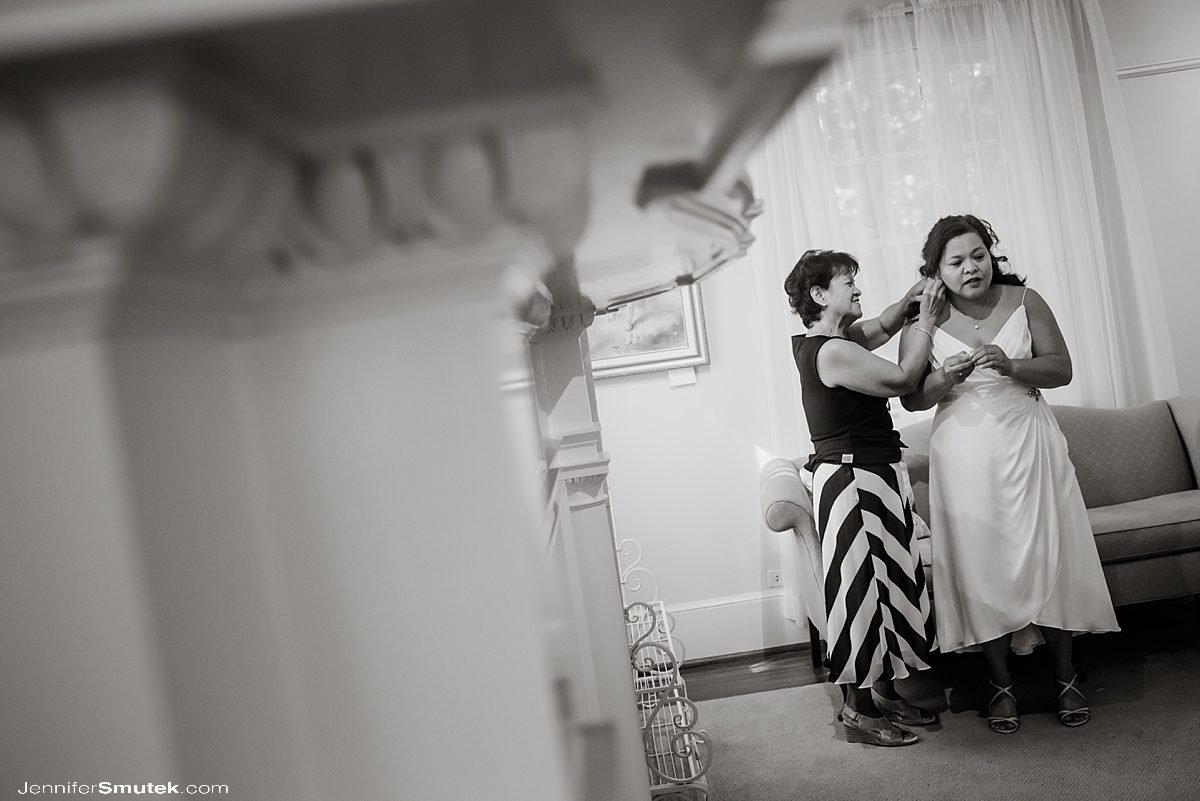 mother helping bride with earrings