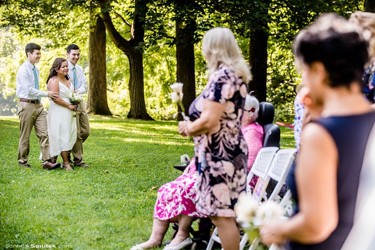 adult sons walking bride down aisle