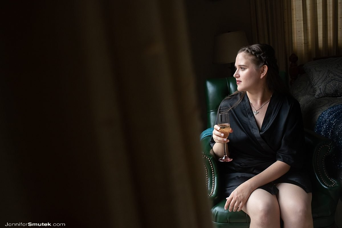 bride sitting at window drinking champange