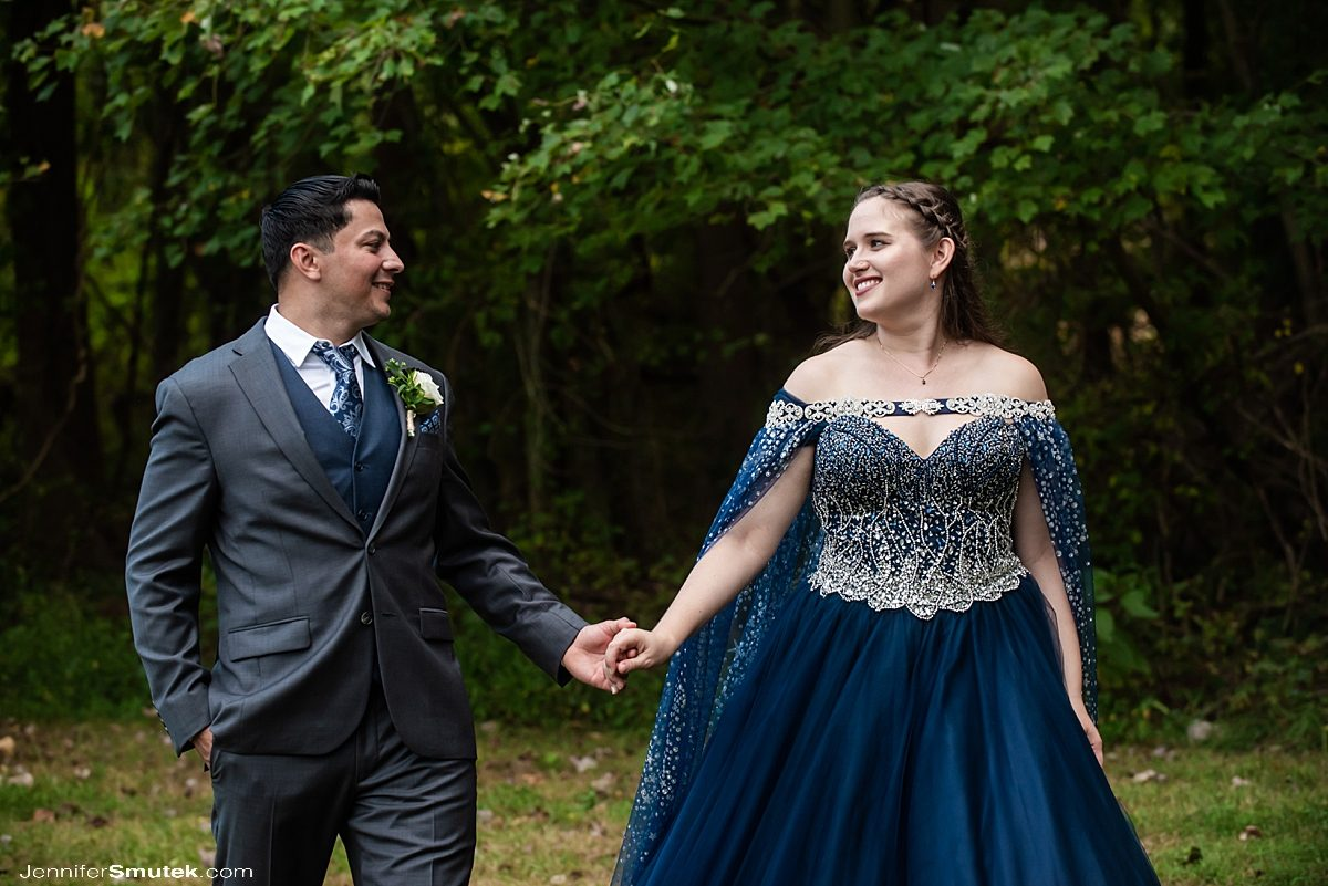 couple walking with a bride in a blue wedding gown