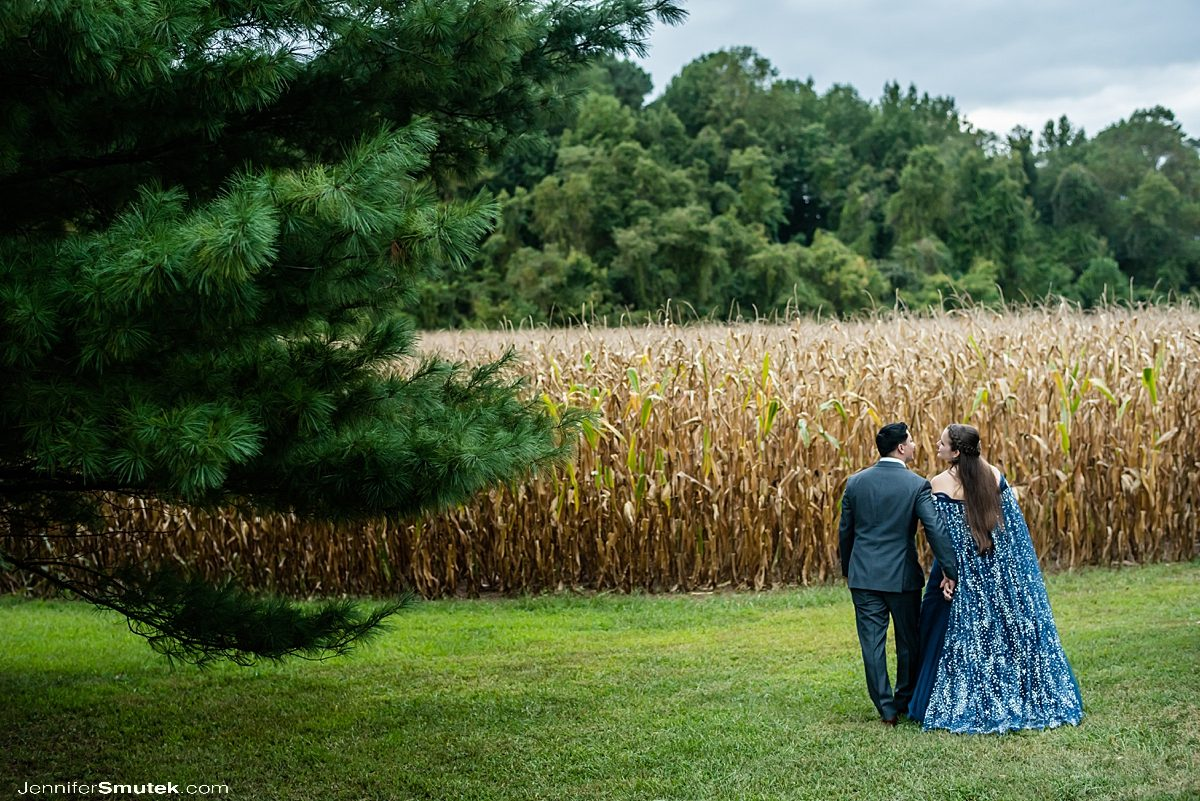 bride and groom walking towards a corn field