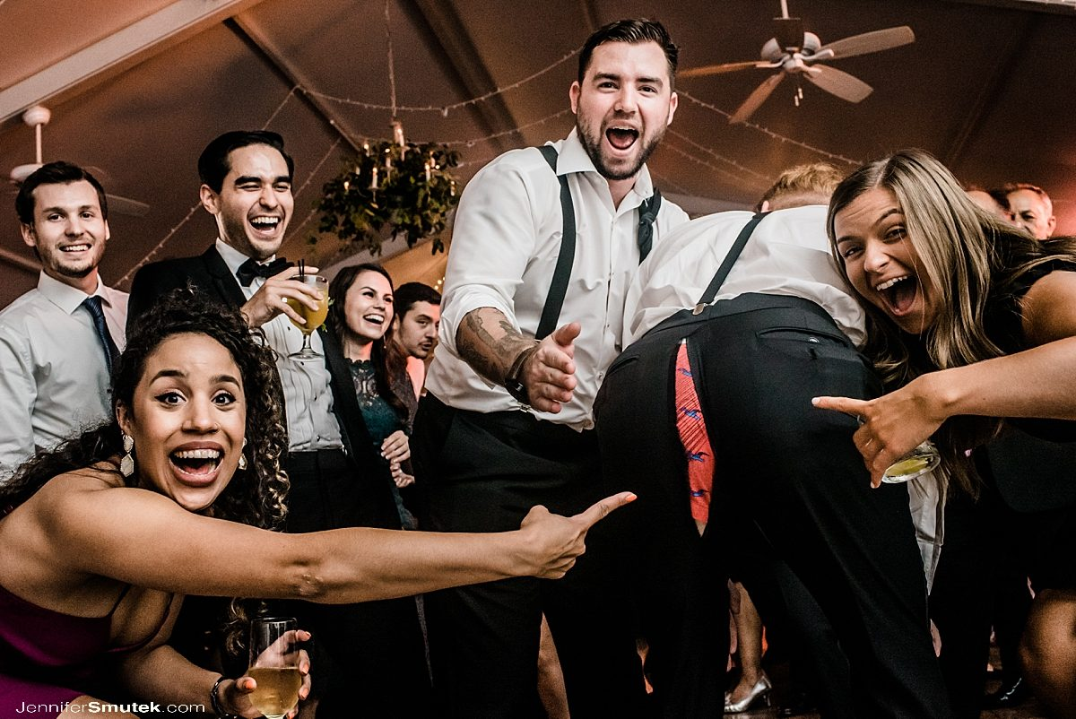 people laughing and pointing at ripped pants at a wedding reception in baltimore