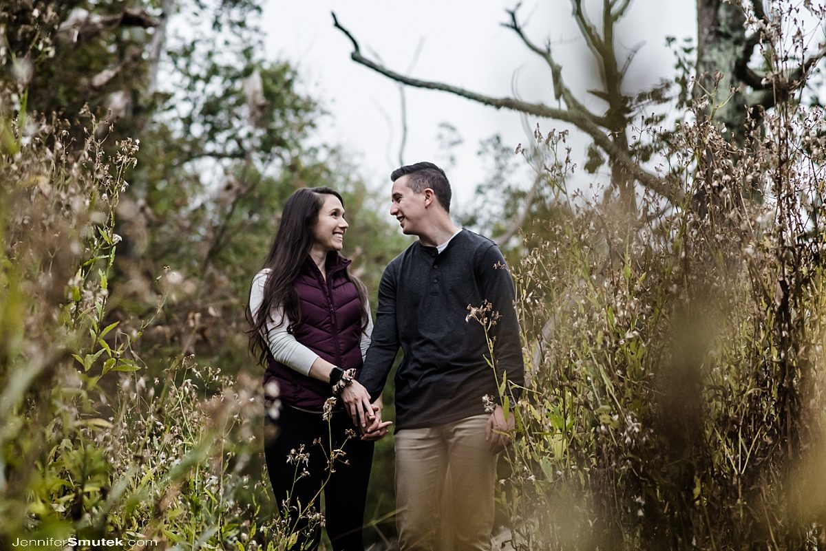 couple walking through wildflowers sugarloaf mountain engagement session