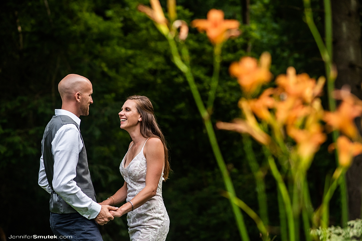 bride and groom laughing in a garden