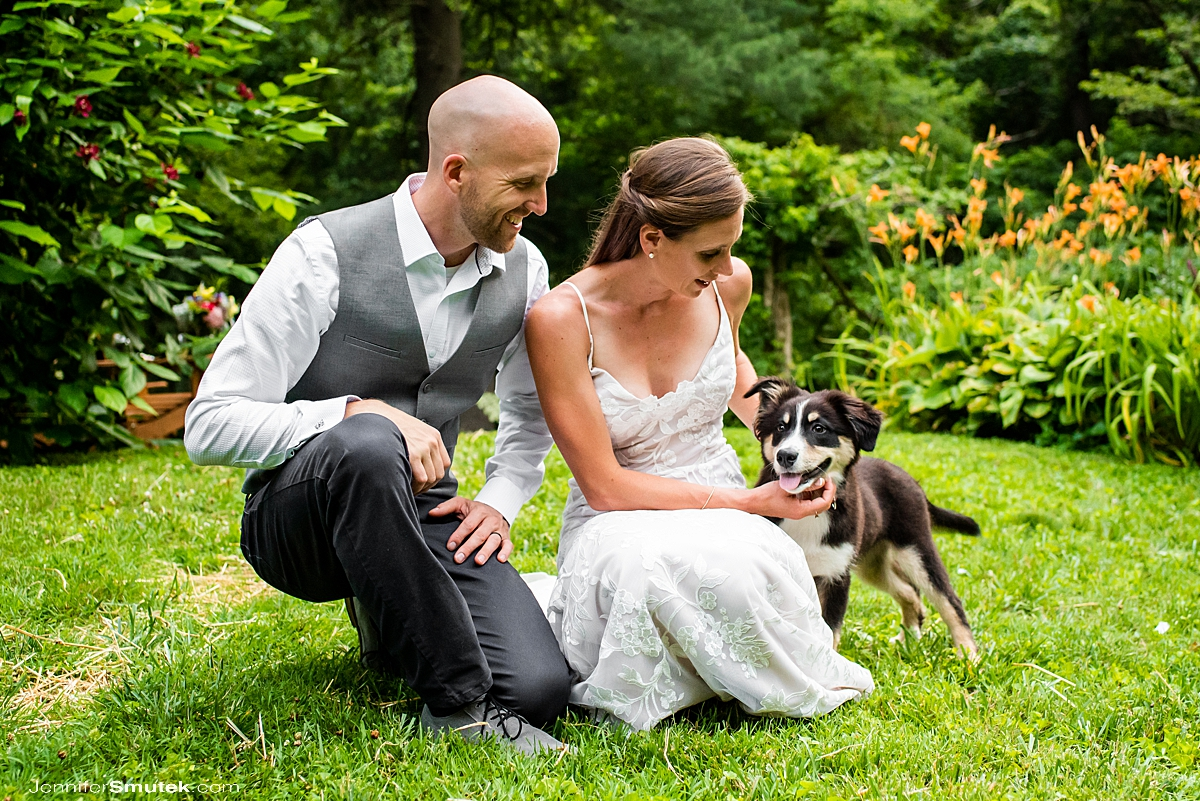 bride and groom with their puppy on their wedding day at a socially distant wedding