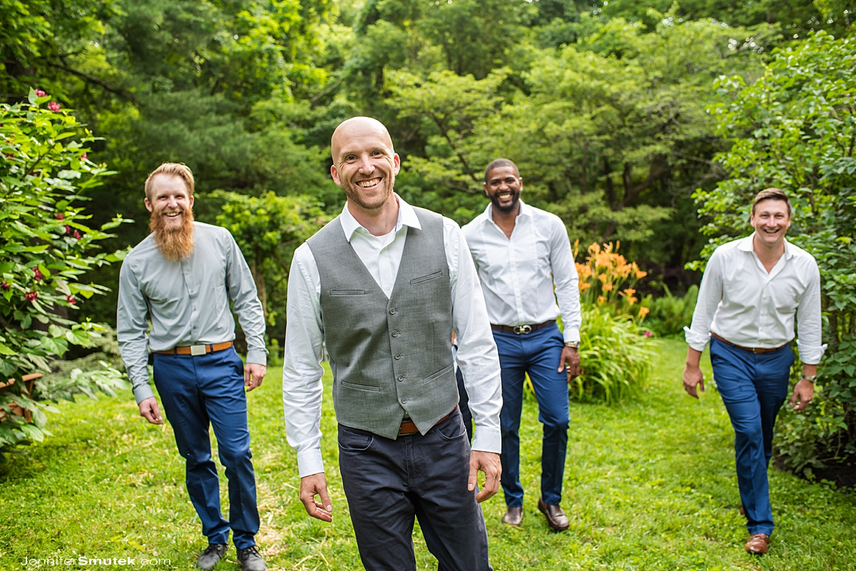 groom and groomsmen walking in a garden