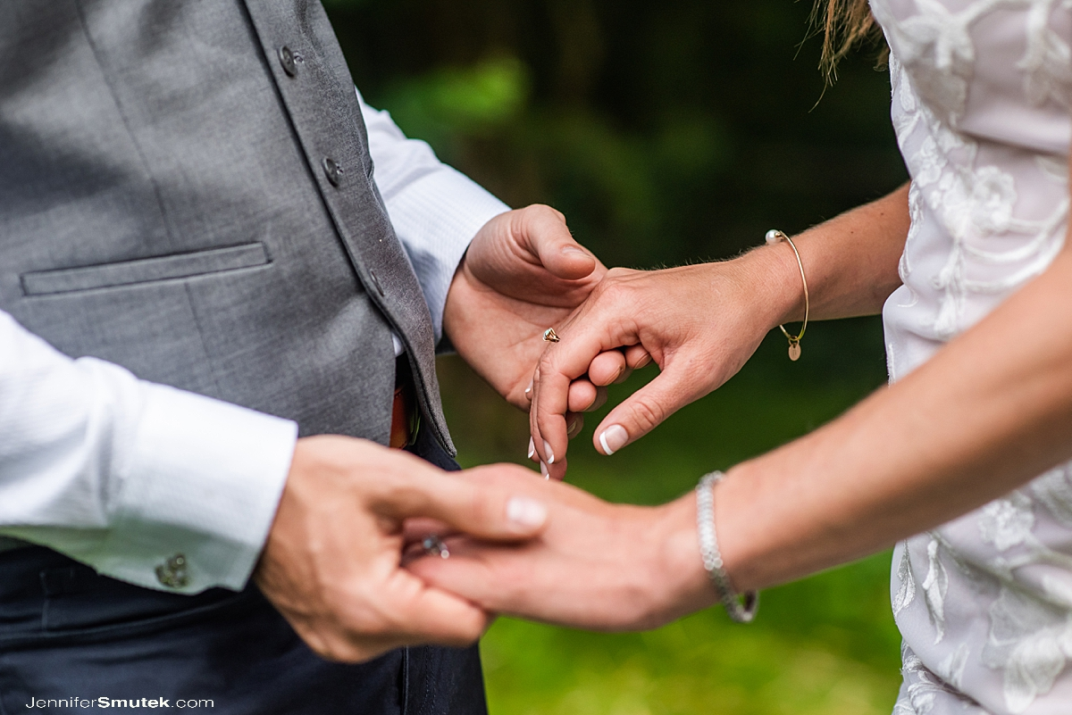 close up of bride and groom holding hands with a turquoise engagement ring during micro wedding in Baltimore