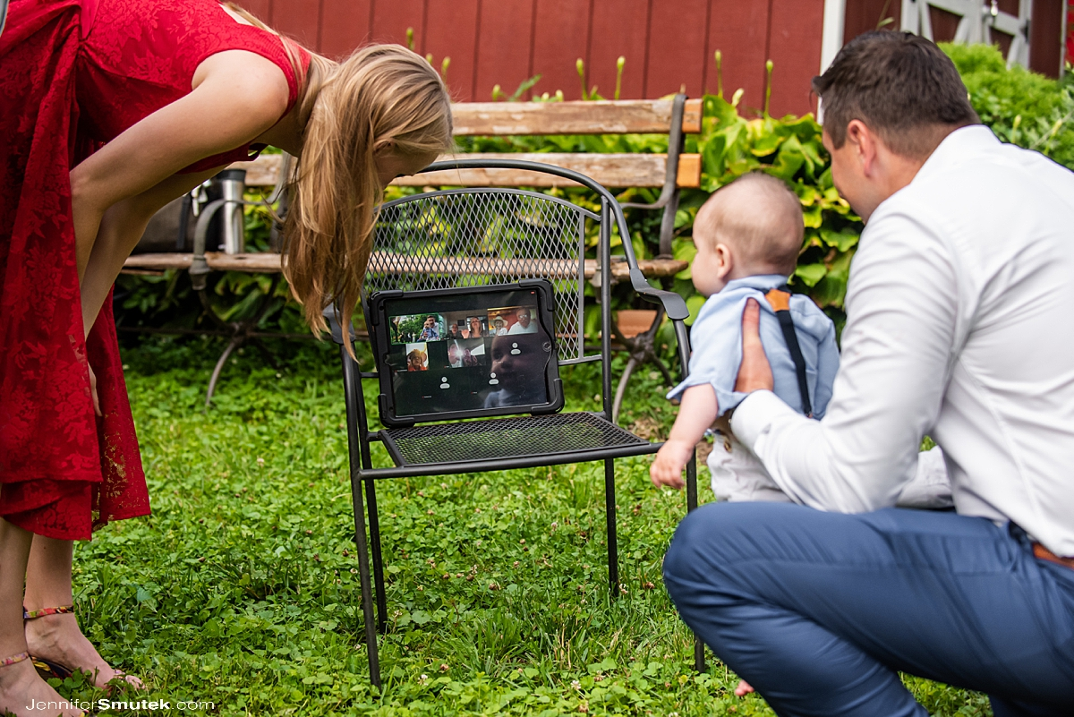 family connecting on an iPad via zoom in a backyard covid-19 wedding maryland