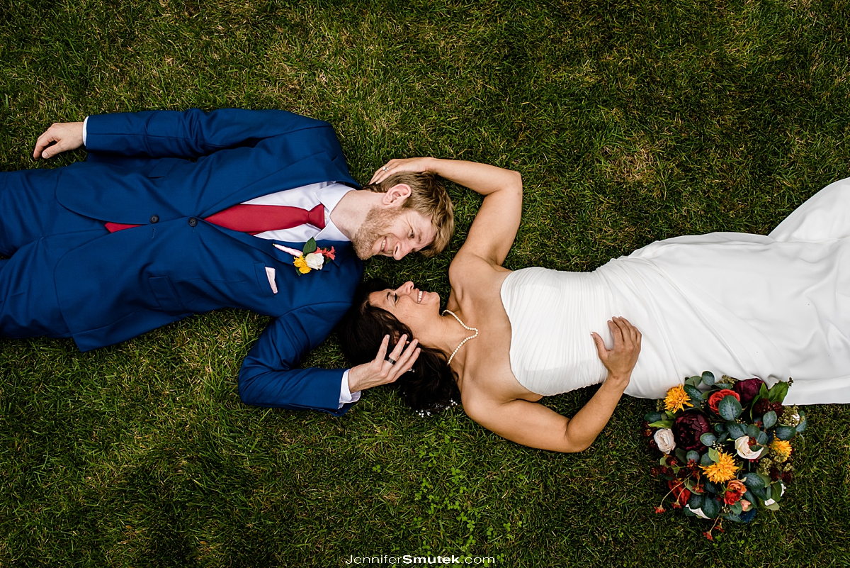bride and groom laying in grass backyard micro wedding