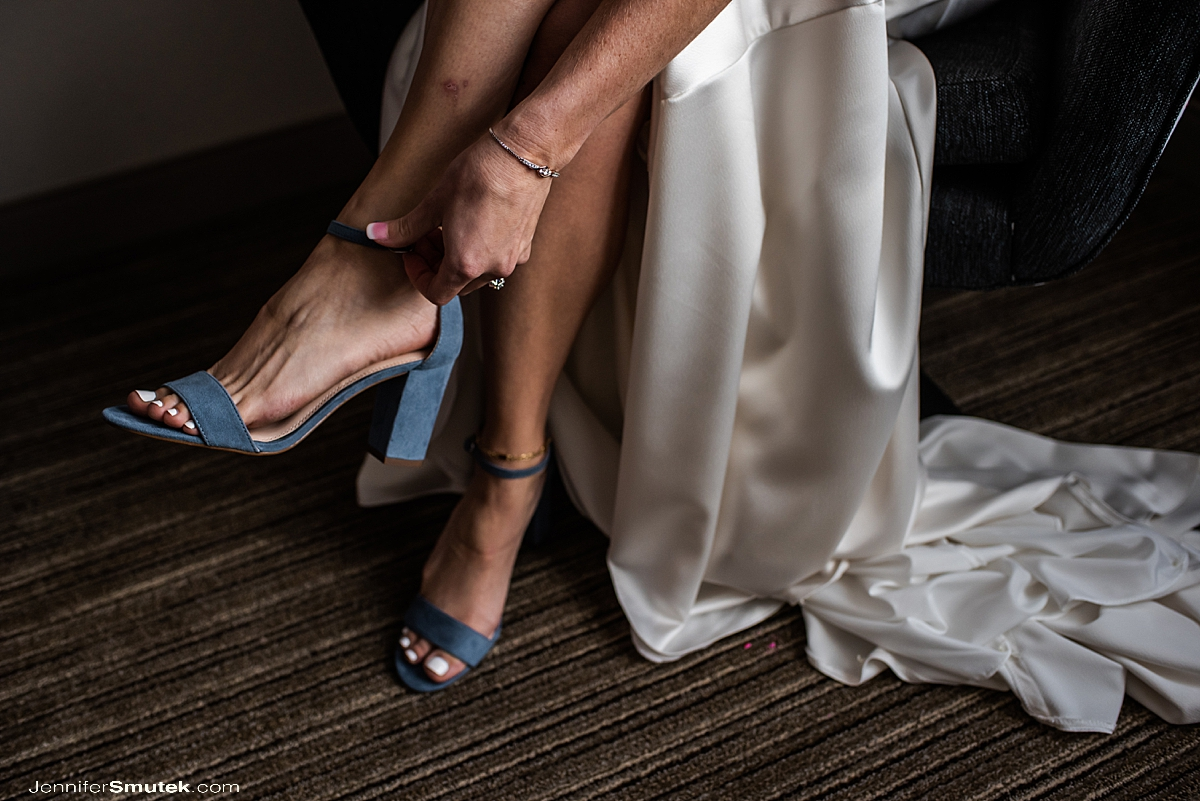 bride putting on blue shoes