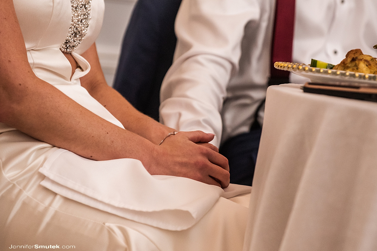 bride and groom holding hands during toasts