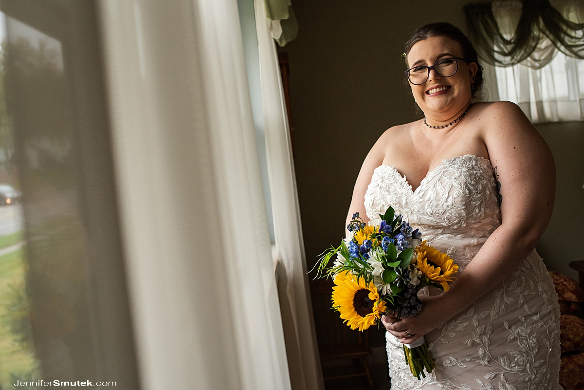 bride in window holding sunflowers