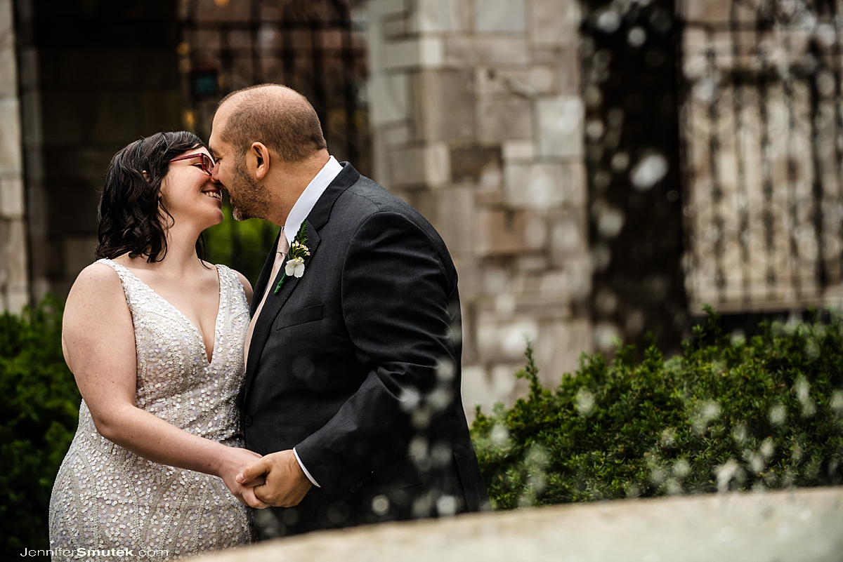 bride and groom kissing in front of st. andrews fountain