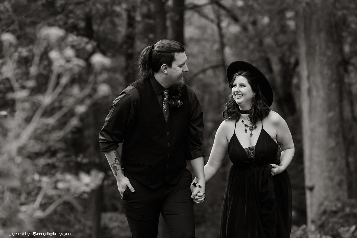black and white of couple walking bride wearing black wedding dress