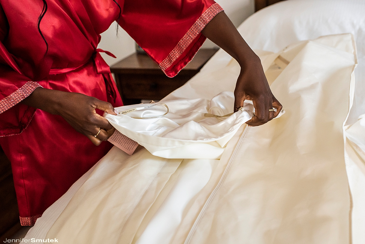 bride getting out her dress wearing a red robe