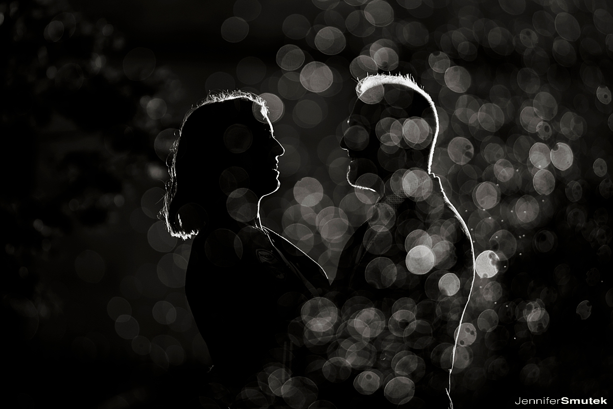 black and white photo of couple holding hands in dramatic light